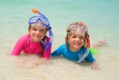 Niños felices que llevan el engranaje que bucea en la playa Foto de archivo