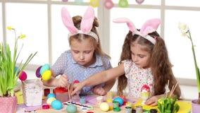 Niños felices que llevan los oídos del conejito que pintan los huevos el día de Pascua almacen de video