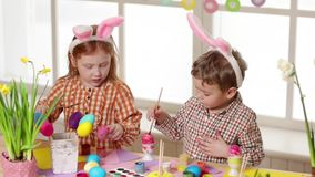 Niños felices que llevan los oídos del conejito que pintan los huevos el día de Pascua metrajes
