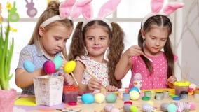 Niños felices que llevan los oídos del conejito que pintan los huevos el día de Pascua almacen de metraje de vídeo