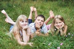 Niños felices que mienten en la hierba Foto de archivo libre de regalías