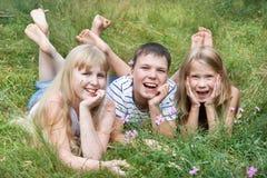 Niños felices que mienten en la hierba Fotos de archivo libres de regalías