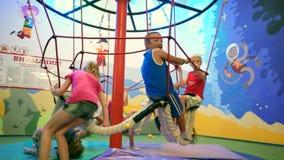 Niños felices que montan el carrusel de la cuerda, grupo de niños que se divierten en cruce giratorio de la cuerda en parque de a metrajes