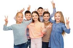 Niños felices que muestran la muestra de la mano de la paz Foto de archivo libre de regalías