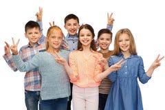 Niños felices que muestran la muestra de la mano de la paz Imagenes de archivo