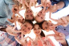 Niños felices que muestran la muestra de la mano de la paz Imagen de archivo
