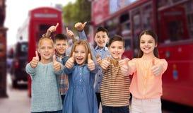 Niños felices que muestran los pulgares para arriba sobre la ciudad de Londres Fotos de archivo libres de regalías