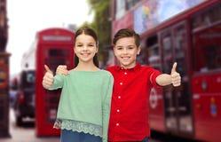 Niños felices que muestran los pulgares para arriba sobre la ciudad de Londres Imagen de archivo libre de regalías