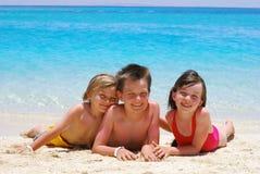 Niños felices que ponen en la playa foto de archivo