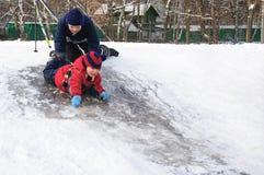 Niños felices que resbalan de una pequeña colina nevosa Foto de archivo libre de regalías