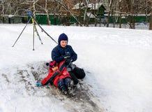 Niños felices que resbalan de una pequeña colina nevosa Imagen de archivo libre de regalías