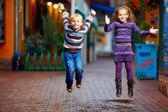Niños felices que saltan debajo de la lluvia Imágenes de archivo libres de regalías