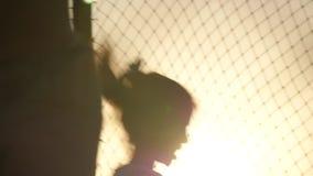 Niños felices que saltan en el trampolín en el fondo de la puesta del sol almacen de video