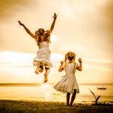 Niños felices que saltan en la playa Imagen de archivo libre de regalías