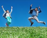 Niños felices que saltan en prado fotografía de archivo