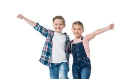 Niños felices que se colocan de abarcamiento con las manos aumentadas y sonrientes en la cámara Imagen de archivo