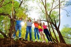 Niños felices que se colocan en árbol caido en el bosque Imagen de archivo