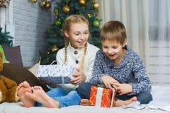 Niños felices que se sientan en cama y que sostienen los regalos Fotos de archivo libres de regalías
