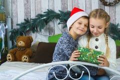 Niños felices que se sientan en cama y que sostienen los regalos Fotografía de archivo libre de regalías