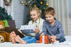 Niños felices que se sientan en cama y que sostienen los regalos Imagen de archivo libre de regalías