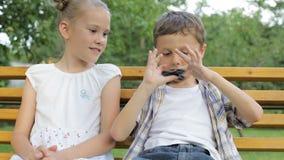 Niños felices que se sientan en el banco en el tiempo del día almacen de metraje de vídeo