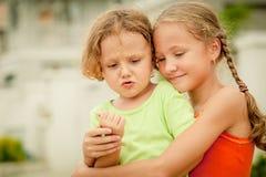 Niños felices que se sientan en el camino Fotos de archivo