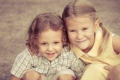 Niños felices que se sientan en el camino Foto de archivo libre de regalías