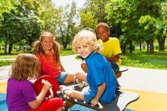 Niños felices que se sientan en el carrusel del patio Imagenes de archivo