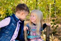 Niños felices que se sientan en la cerca Facing Each Other Imagenes de archivo