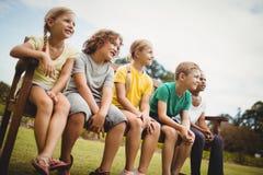 Niños felices que se sientan en un banco Fotos de archivo libres de regalías