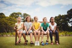 Niños felices que se sientan en un banco Foto de archivo