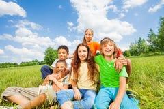 Niños felices que se sientan junto en un cierre del abrazo imagen de archivo