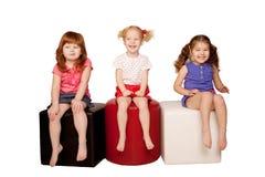 Niños felices que se sientan y que ríen. Fotos de archivo