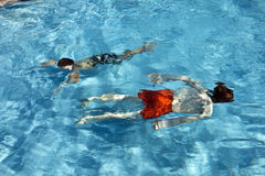 Niños felices que se zambullen en la piscina Fotos de archivo libres de regalías
