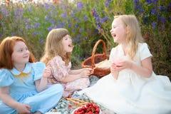 Niños felices que tienen comida campestre al aire libre Sonrisa de las novias y j Fotografía de archivo