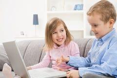 Niños felices que usan la computadora portátil Imagenes de archivo