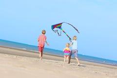 Niños felices que vuelan la cometa en la playa Fotografía de archivo