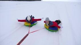 Niños felices sledding en invierno un tubo inflable de la nieve y que agitan sus manos los niños ríen y disfrutan Chica foto de archivo