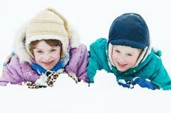 Niños felices sonrientes en la nieve del invierno al aire libre Fotos de archivo libres de regalías