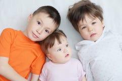 Niños felices, tres edades de los niños diversas que mienten, retrato del muchacho, niña y bebé, felicidad en la niñez de hermano fotos de archivo