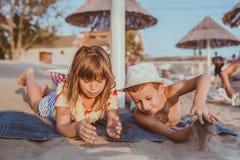 Niños felices y el jugar con la arena fotos de archivo