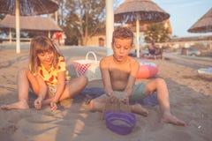 Niños felices y el jugar con la arena en la playa imágenes de archivo libres de regalías