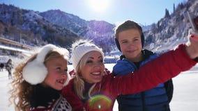 Niños felices y madre que hacen el selfie por el teléfono móvil, patinaje de hielo metrajes
