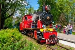 Niños ferroviarios con la locomotora de vapor roja fotografía de archivo