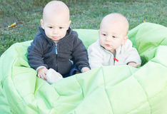 Niños gemelos que se sientan en Bean Bag Foto de archivo libre de regalías