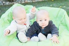 Niños gemelos que se sientan en Bean Bag Imágenes de archivo libres de regalías