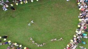 Niños hermosos aéreos del baile en la hierba en un día de fiesta de la naturaleza y de la reconstrucción almacen de metraje de vídeo