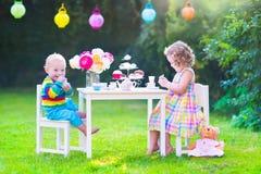 Niños hermosos en la fiesta del té de la muñeca Imágenes de archivo libres de regalías