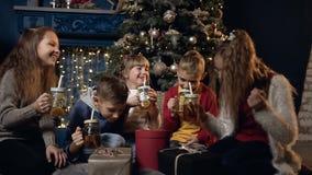 Niños hermosos felices que beben té y que ríen en el cuarto acogedor de la Navidad almacen de video