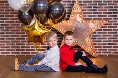 Niños hermosos, niños pequeños que celebran cumpleaños y que soplan velas en la torta cocida hecha en casa, interior Fiesta de cu Fotografía de archivo libre de regalías
